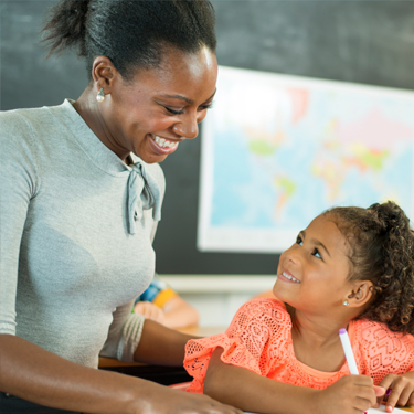 A female teacher in a classroom with her young student